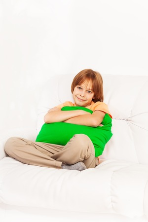 One happy smiling and relaxed boy 10 years old sitting with pillow on the white leather sofa Stock Photo - 22511616