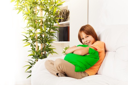 One happy shy little boy years 10 old sitting hugging pillow on the white leather coach in living room at home Stock Photo - 22511617