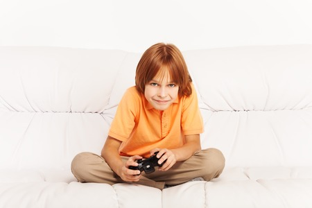 kids playing video games: Happy Caucasian boy playing video games holding game controller sitting on the coach in living room Stock Photo