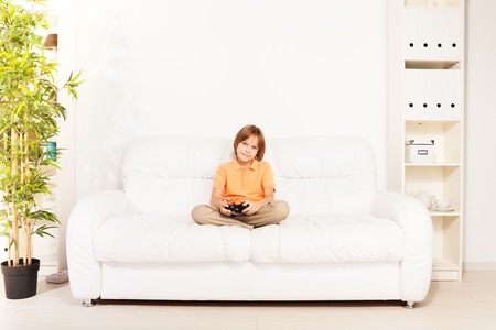 Happy smiling Caucasian boy gamer playing video games holding game controller sitting on the white sofa in living room photo
