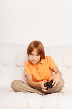 gamepad: Little boy with tense expression holding game controller of videogame sitting on the coach Stock Photo