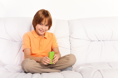 Little Caucasian boy with amazing big smile  SMS her friends sitting on the coach in living room photo