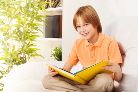 Close-up portrait of smart smiling Caucasian boy portrait in interior sitting on the sofa at home and reading photo