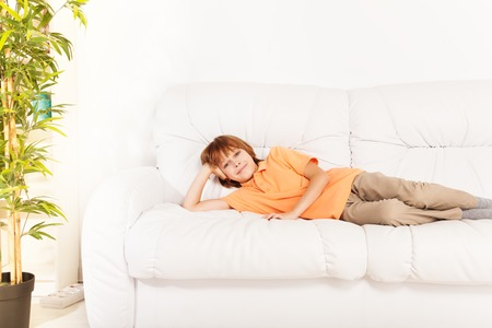 10 years old: One happy smiling relaxed boy 10 years old laying on the sofa at home coach