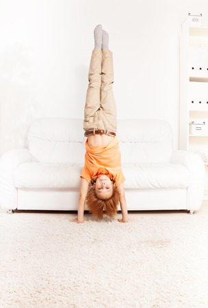 Cute little boy standing on the hands in living room by coach photo