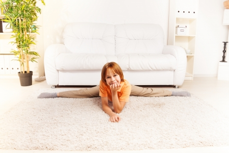 boy gymnast: Little boy laying on the floor in twine pose and looking at camera in living room