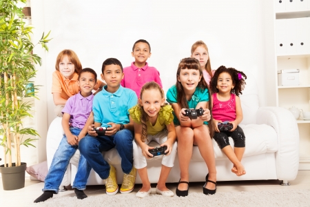 kids playing video games: Group of diversity looking kids, boys and girls playing videogame sitting on the sofa holding game controllers