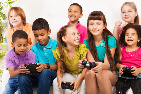 videogame: Close portrait of a group of diversity looking kids, boys and girls playing videogame sitting on the sofa holding game controllers, talking and laughing