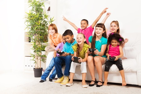 videogame: Close portrait of a group of diversity looking kids, boys and girls playing videogame sitting on the couch in living room holding game controllers, talking and laughing