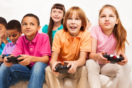 videogame: Close portrait of a group of diversity looking kids, boys and girls playing videogame Stock Photo
