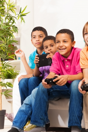 videogame: Close portrait of a group of diversity looking children boys and girls, friends, playing videogame sitting on the sofa in living room