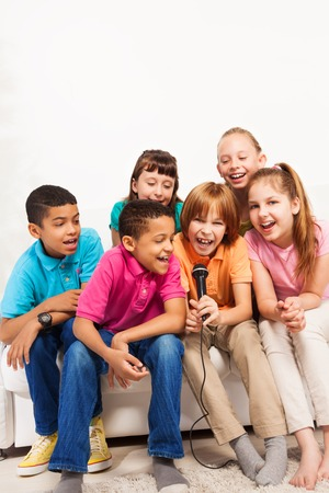 singing girl: Group of happy kids, boys and girls, singing on karaoke together sitting on the coach in living room