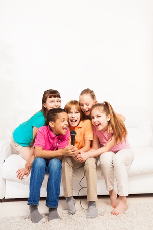 chorus: Group of happy exited diversity looking kids, boys and girls, singing together sitting on the coach in living room