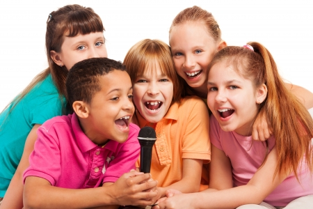 child singing: Close-up of a group of happy exited diversity looking kids, boys and girls, singing together sitting on the coach in living room