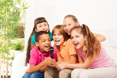 Close-up shoot of group of five happy little kids, boys and girls, singing together sitting on the coach in living room at home photo