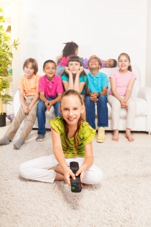 Little girl with TV remote control sitting on the floor in living room with her friends sitting on the coach on background photo