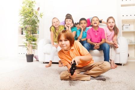 niños jugando videojuegos: Niño feliz de 10 años jugando juegos de video que sostienen el regulador del juego sentado en el suelo con sus amigos en el fondo en el sofá blanco de la sala de estar