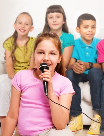 child singing: Close portrait happy beautiful girl sitting on the floor and singing to microphone with group of friends, boys and girls sitting on the coach on background Stock Photo