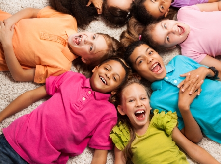 Group of happy diversity looking kids laying in star shape on the floor Stock Photo