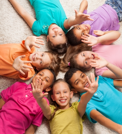 lying down on floor: Group of happy diversity looking kids laying in star shape on the floor with lifted kids