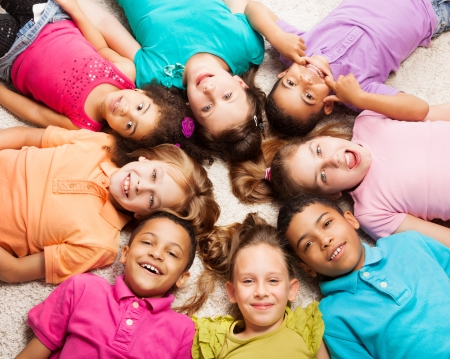 lying down on floor: Group of eight happy diversity looking kids, boys and girls laying in star shape on the floor Stock Photo