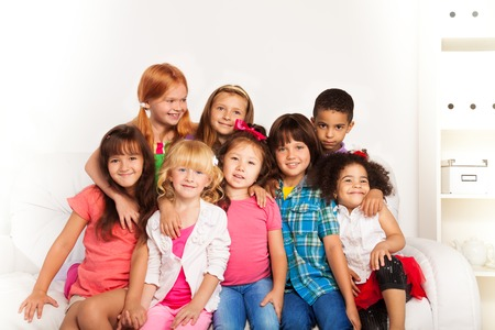kids hugging: Group of little kids sitting on a couch and smiling, hugging together at home interior Stock Photo