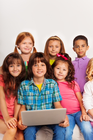 Close portrait of large group of kids sitting with laptop on the coach and smiling photo