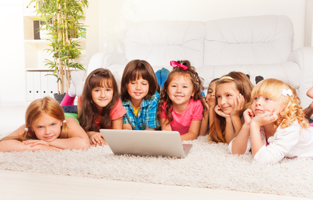 six girls: Group of happy little kids, boys and girls laying on the floor with laptop in living room