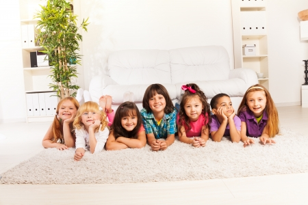 Group of eight little kids, boys and girls, Asian and Caucasian laying on the floor at home in living room looking at camera with sofa on background photo