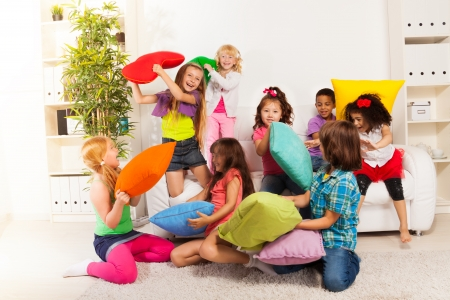 Pillow fight - large group of kids, boys and girls playing in the living room hitting each other with colorful pillows Stock Photo