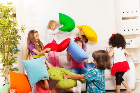 indoors: Pillow fight - large group of kids actively playing with pillow in the living room on the coach Stock Photo