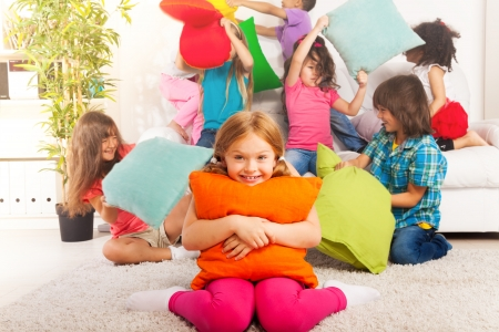 Happy smiling little girl hugging pillow with large group of her friends pillow fighting on the background photo