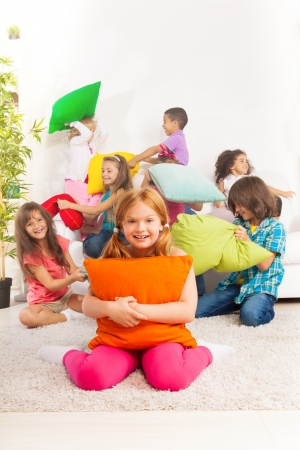 Pillow fight: Happy smiling little girl hugging pillow with large group of her friends fighting with pillow on the coach Stock Photo