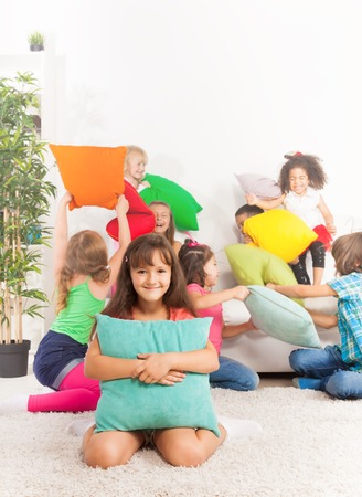 Pillow fight - on happy little Caucasian girl with pillow and her friends fighting on background  photo
