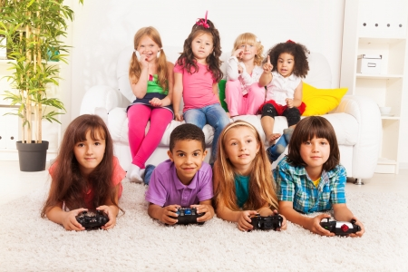 Close portrait of a group of diversity looking kids, boys and girls playing videogame laying on the floor in kids room photo
