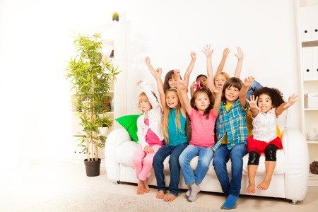 lifted hands: Group of eight happy little 5-6 years old kids, boys and girls, black, Asian and Caucasian sitting on the coach with with lifted hands and happy faces  Stock Photo