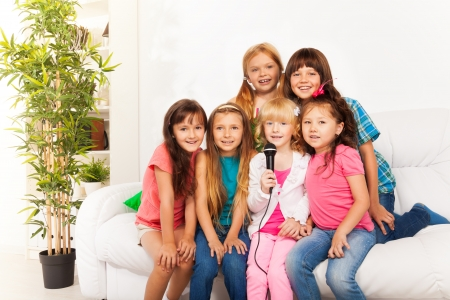 child singing: Group of five happy little kids, boys and girls, singing together sitting on the coach in living room at home
