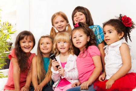 sing: Large group of five happy little kids, boys and girls, singing together sitting to microphone on the sofa in living room at home