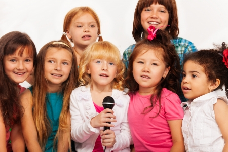 child singing: Close-up shoot of a large group of five happy little kids, boys and girls, singing together sitting to microphone on the coach at home