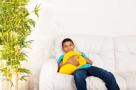 10 years old: One happy black smiling boy 10 years old sitting with vivid yellow pillow sitting on the white leather coach in living room at home