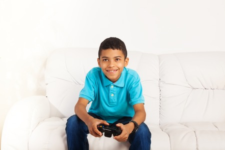 niños jugando videojuegos: Feliz niño negro sonriente jugando videojuegos celebración de dispositivo de juego que se sienta en el coche en el salón Foto de archivo