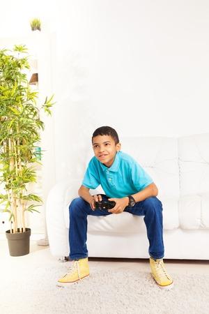 jugando videojuegos: Feliz negro niño de 10 años de edad, jugar juegos de video que sostienen el regulador del juego que se sienta en el sofá blanco de la sala de estar