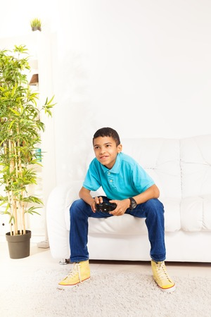 kids playing video games: Happy black 10 years old boy playing video games holding game controller sitting on the white sofa in living room