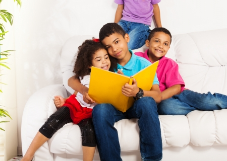 brother and sister: Family, group of four kids with older brother reading books to brothers and sister hugging little girl
