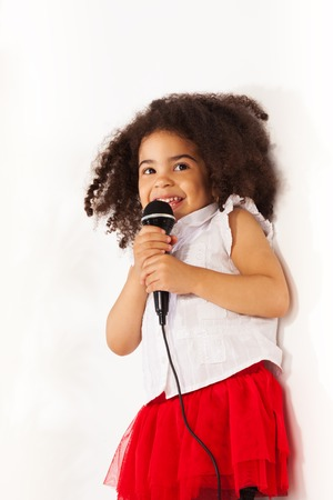 Close-up portrait of cute little black African three years old girl with microphone  photo