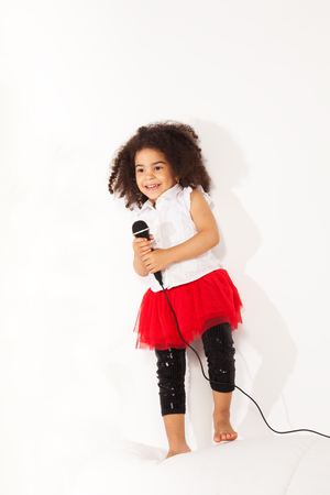 child singing: Cute little black African three years old girl with cute curly black hair with microphone performing standing on the coach and dancing