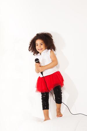 niño cantando: Cute little negros africanos niña de tres años con lindo pelo negro rizado de pie con el micrófono de realizar en el coche y el baile