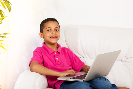 kids laptop: Nice black boy sitting with laptop on the couch in happy mood and looking at camera