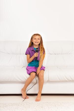 five years old: Caucasica bambino piccolo di cinque anni ragazza con i capelli biondi che canta lungo per microfono eseguire seduti sul pullman