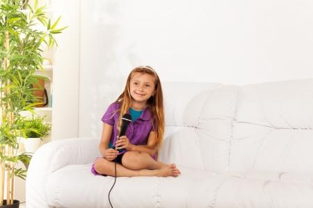 five years old: Caucasica bambino piccolo di cinque anni ragazza con i capelli biondi che canta lungo per microfono eseguendo seduto sul divano in salotto